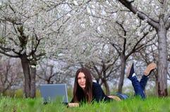 La muchacha en el jardín florecido que pone con un ordenador portátil Imagen de archivo libre de regalías
