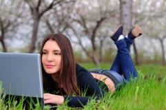 La muchacha en el jardín florecido que pone con un ordenador portátil Fotos de archivo libres de regalías