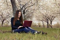 La muchacha en el jardín florecido que se sienta con un ordenador portátil Imágenes de archivo libres de regalías