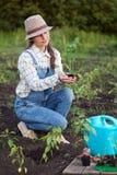 La muchacha en el jardín hace el establecimiento de las semillas Imagenes de archivo