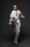 La muchacha en el kimono blanco golpea la pierna con el pie correcta delantera Imagen de archivo
