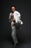 La muchacha en el kimono blanco golpea la pierna con el pie izquierda delantera Imágenes de archivo libres de regalías