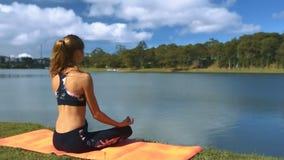 La muchacha en el lago watches de la actitud de la yoga y las nubes reflejan