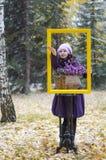 La muchacha en el marco y en el bosque, coge la primera nieve en la palma de foto de archivo libre de regalías