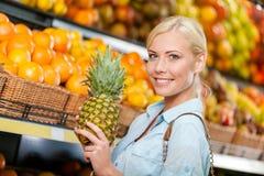 La muchacha en el mercado que elige las frutas da la piña imagen de archivo