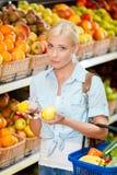 La muchacha en el mercado que elige las frutas da los limones Imagen de archivo