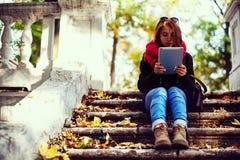 La muchacha en el otoño en el parque Hojas caidas amarillas y rojas, arquitectura antigua La muchacha se está sentando en las esc foto de archivo