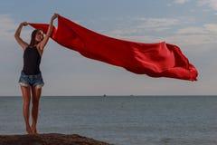 La muchacha en el paño del rojo del whith de la playa fotografía de archivo