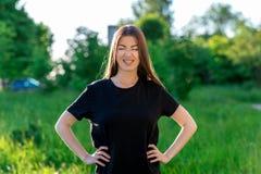 La muchacha en el parque es una morenita en aire fresco en una camiseta negra Centelleo con placer Sonrisa con los apoyos en Fotos de archivo libres de regalías