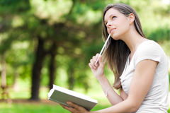 La muchacha en el parque escribe en su diario imagenes de archivo