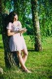 La muchacha en el parque escribe en su diario personal Imagenes de archivo