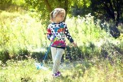 La muchacha en el parque hermoso, con una red coge mariposas, las sonrisas y las risas, humor juguetón, bromas infantiles fotografía de archivo