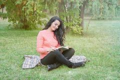 La muchacha en el parque lee un libro imagenes de archivo
