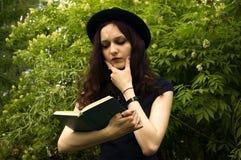 La muchacha en el parque que lee un libro Imágenes de archivo libres de regalías