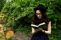 La muchacha en el parque que lee un libro Imagenes de archivo