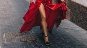 La muchacha en el rojo De largo, piernas delgadas imágenes de archivo libres de regalías