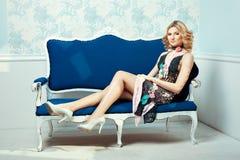 La muchacha en el sofá en un vestido hecho punto Fotos de archivo libres de regalías