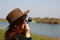 La muchacha en el sombrero con la cámara imagenes de archivo