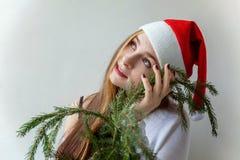 La muchacha en el sombrero de Papá Noel con el abeto del verde de la Navidad ramifica Fotos de archivo libres de regalías