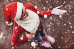 La muchacha en el sombrero de Papá Noel, copos de nieve de cogida de la mujer bastante joven Foto de archivo