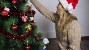 La muchacha en el sombrero de santa adorna un árbol de navidad almacen de video