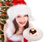 La muchacha en el sombrero de santa come la torta por el árbol de navidad. Fotos de archivo