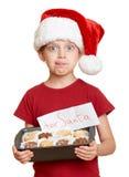La muchacha en el sombrero de santa con las galletas se lame - concepto de la Navidad de las vacaciones de invierno Imagen de archivo