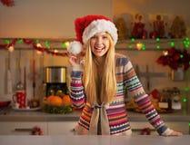 La muchacha en el sombrero de santa en la Navidad adornó la cocina Imágenes de archivo libres de regalías