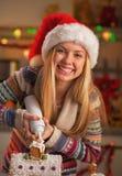 La muchacha en el sombrero de santa que adornaba el housewith de la galleta azotó la crema Fotos de archivo