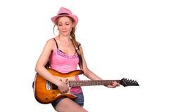 La muchacha en el sombrero del rosa toca la guitarra Imagenes de archivo
