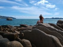 La muchacha en el sombrero que se sienta en la bahía de Acapulco oscila Imagen de archivo libre de regalías