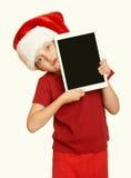 La muchacha en el sombrero rojo de santa con la PC de la tableta en blanco aislada, amarillea entonado Foto de archivo