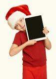 La muchacha en el sombrero rojo de santa con PC de la tableta, amarillea entonado Foto de archivo