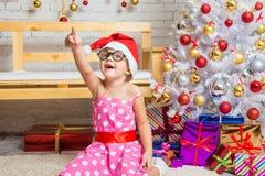 La muchacha en el sombrero rojo y los vidrios redondos divertidos señala un finger en algo interesante Foto de archivo libre de regalías