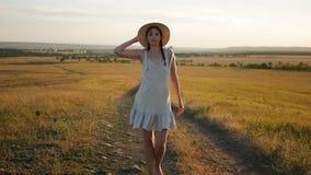 La muchacha en el sombrero y el vestido está en el campo en la puesta del sol almacen de video