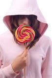 La muchacha en el suéter rosado sostiene el lollipop grande Fotos de archivo libres de regalías