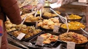 La muchacha en el supermercado elige una comida lista El vendedor sirve al comprador almacen de metraje de vídeo