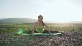 La muchacha en el top de la montaña realiza estirar y la relajación de los músculos después de un entrenamiento duro Aptitud y yo almacen de video