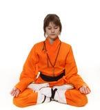 La muchacha en el traje anaranjado se está sentando en la meditación Foto de archivo
