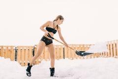 La muchacha en el traje de baño lanza nieve con una pala Foto de archivo