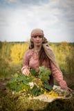 La muchacha en el traje eslavo de Viking Age teje una guirnalda fotos de archivo libres de regalías