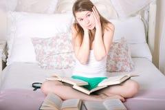 Muchacha en la cama que lee un libro Imagen de archivo