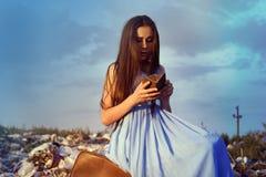 La muchacha en el vertido se sienta en una maleta vieja con un monedero vacío contra el cielo azul Fotos de archivo