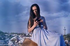 La muchacha en el vertido se sienta en una maleta vieja con un monedero vacío contra un cielo azul Foto de archivo libre de regalías