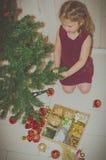 La muchacha en el vestido adorna un árbol de navidad Fotografía de archivo