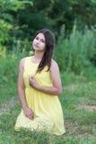 La muchacha en el vestido amarillo que se sienta en hierba Fotografía de archivo libre de regalías