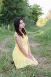 La muchacha en el vestido amarillo que se sienta en hierba Imagen de archivo