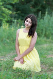 La muchacha en el vestido amarillo que se sienta en hierba Fotos de archivo libres de regalías