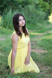 La muchacha en el vestido amarillo que se sienta en hierba Fotos de archivo
