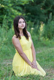 La muchacha en el vestido amarillo que se sienta en hierba Imagenes de archivo